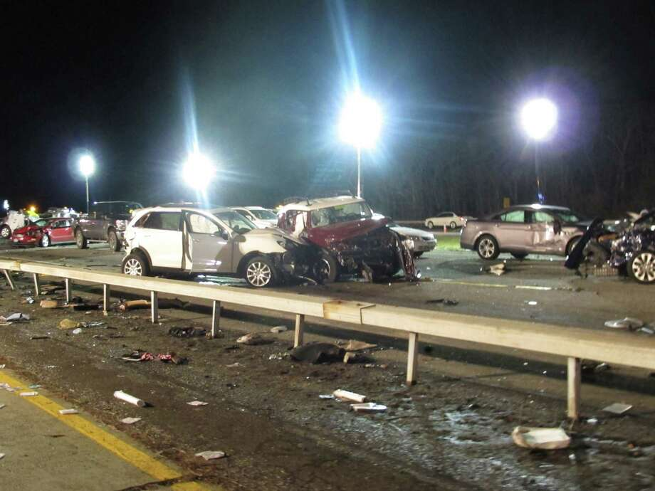 Damaged vehicles and debris are strewn across the Long Island Expressway following a chain reaction crash on Wednesday, Dec. 19, 2012, in Shirley, N.Y. At least one person was killed and 32 injured. Photo: Frank Eltman, AP / AP