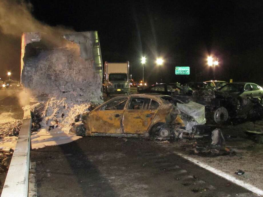A tractor-trailer still smolders hours after a chain-reaction crash on the Long Island Expressway on Wednesday, Dec. 19, 2012 in Shirley, N.Y. At least one person was killed and 32 others were injured in the pileup, which involved about two dozen vehicles. Photo: Frank Eltman, AP / AP