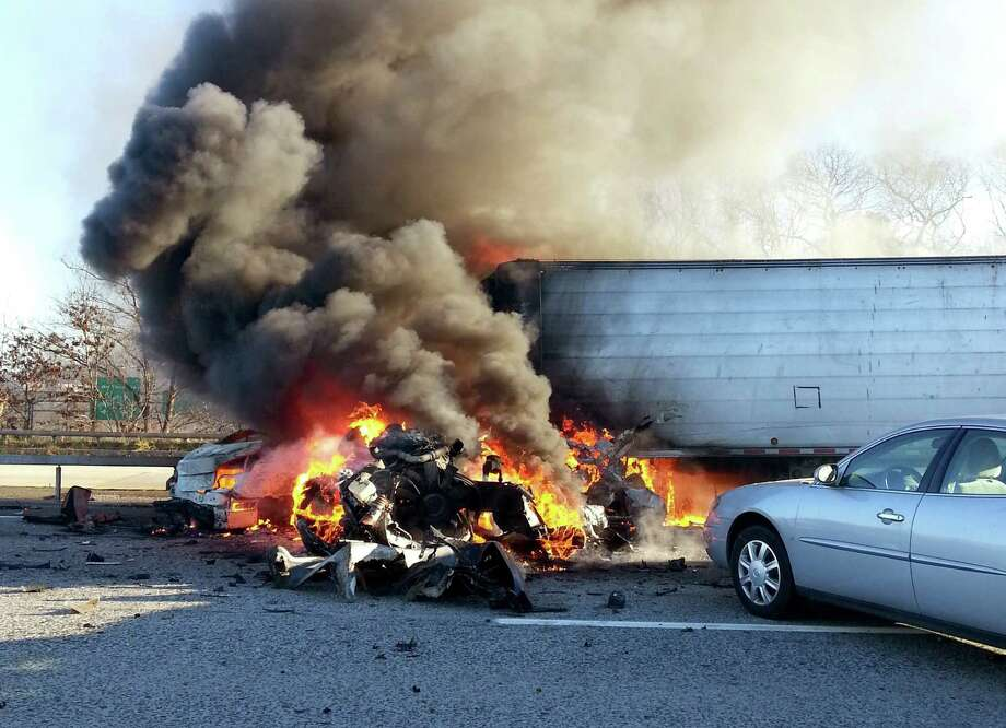 Flames engulf a passenger car and a tractor-trailer on the Long Island Expressway in Shirley, N.Y., Wednesday, Dec. 19, 2012. Police say one person has died and 32 people were injured in the massive traffic pileup that left dozens of vehicles littered across the main freeway on New York's Long Island. (AP Photo/Newsday, James Carbone) NYC OUT, NO SALES Photo: James Carbone, AP / Newsday