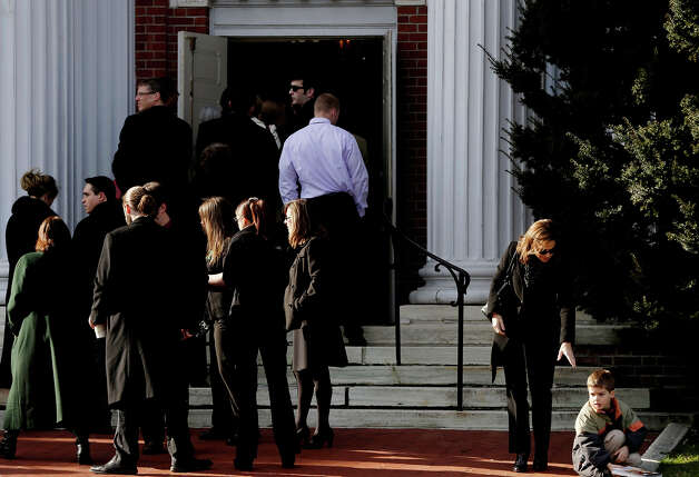 A woman offers her hand to a boy before entering a church for the memorial service for Lauren Rousseau in Danbury, Conn., Thursday, Dec. 20, 2012.   Rousseau, 30, was killed when Adam Lanza walked into Sandy Hook Elementary School in Newtown, Dec. 14, and opened fire, killing 26 people, including 20 children, before killing himself. Photo: AP
