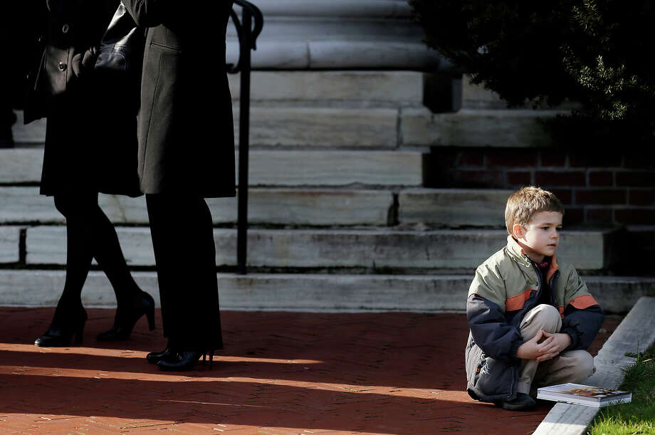A boy sits near the steps of a church a church  before the memorial service for Lauren Rousseau in Danbury, Conn., Thursday, Dec. 20, 2012.   Rousseau, 30, was killed when Adam Lanza walked into Sandy Hook Elementary School in Newtown, Dec. 14, and opened fire, killing 26 people, including 20 children, before killing himself. Photo: AP
