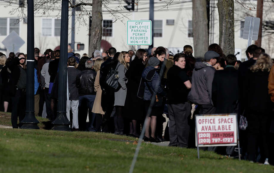 A man, left, looks over the long line to enter a church before a memorial service for Lauren Rousseau in Danbury, Conn., Thursday, Dec. 20, 2012.   Rousseau, 30, was killed when Adam Lanza walked into Sandy Hook Elementary School in Newtown, Dec. 14, and opened fire, killing 26 people, including 20 children, before killing himself. Photo: AP