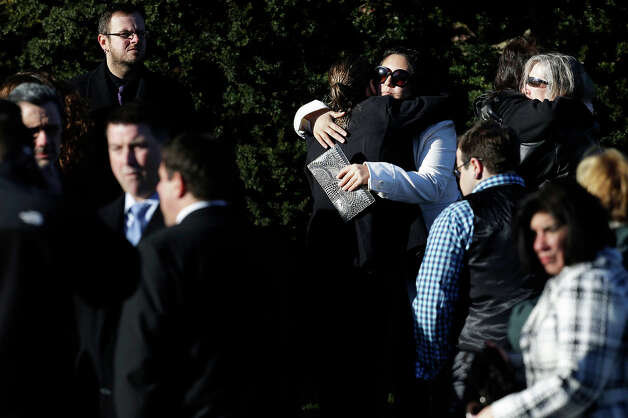 People hug as they wait outside of the First Congregational Church before a memorial service for Lauren Rousseau in Danbury, Conn., Thursday, Dec. 20, 2012.   Rousseau, 30, was killed when Adam Lanza walked into Sandy Hook Elementary School in Newtown, Dec. 14, and opened fire, killing 26 people, including 20 children, before killing himself. Photo: AP