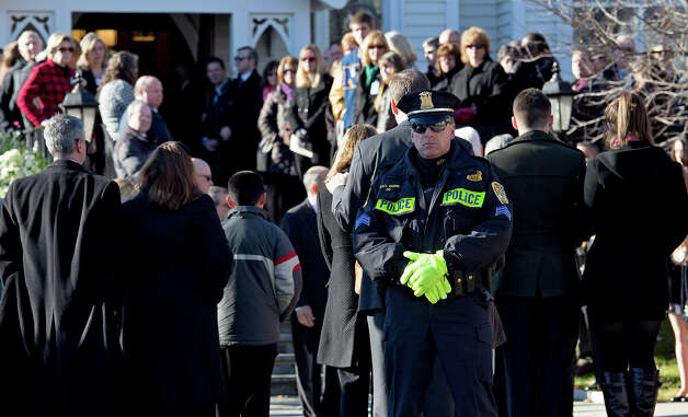 A police officer stands outside as a service begins for teacher Anne Marie Murphy at the St. Mary Of The Assumption Church in Katonah, N.Y. Thursday, Dec. 20, 2012. Murphy was killed when gunman, Adam Lanza, walked into Sandy Hook Elementary School in Newtown, Conn., Dec. 14, and opened fire, killing 26, including 20 children, before killing himself. Photo: AP