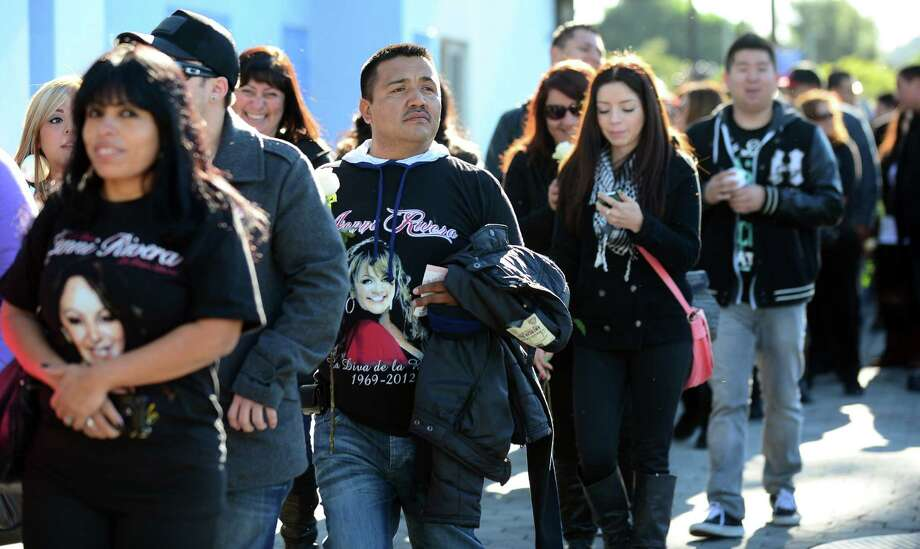 """Fans of the late Mexican-American singer Jenni Rivera walk in line with their tickets to attend the memorial service at the Gibson Amphitheater in Universal City on December 19, 2012 in California. The service, billed by the Rivera family as a """"Celestial Graduation,'' was broadcast live and watched by her many fans off a big screen at a Universal CityWalk plaza. Photo: FREDERIC J. BROWN, AFP/Getty Images / AFP"""