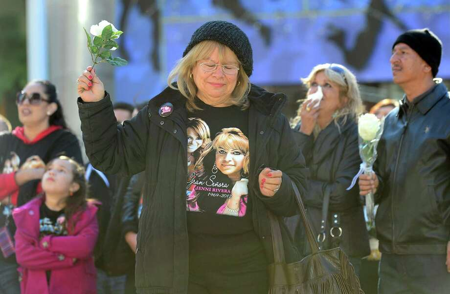 "Fans of the late Mexican-American singer Jenni Rivera mourn her death while watching a live viewing of the memorial service at the Gibson Amphitheater in Universal City on December 19, 2012 in California, attended by those with tickets. The service, billed by the Rivera family as a ""Celestial Graduation,'' was broadcast live and watched by her many fans off a big screen at a Universal CityWalk plaza. Photo: FREDERIC J. BROWN, AFP/Getty Images / AFP"