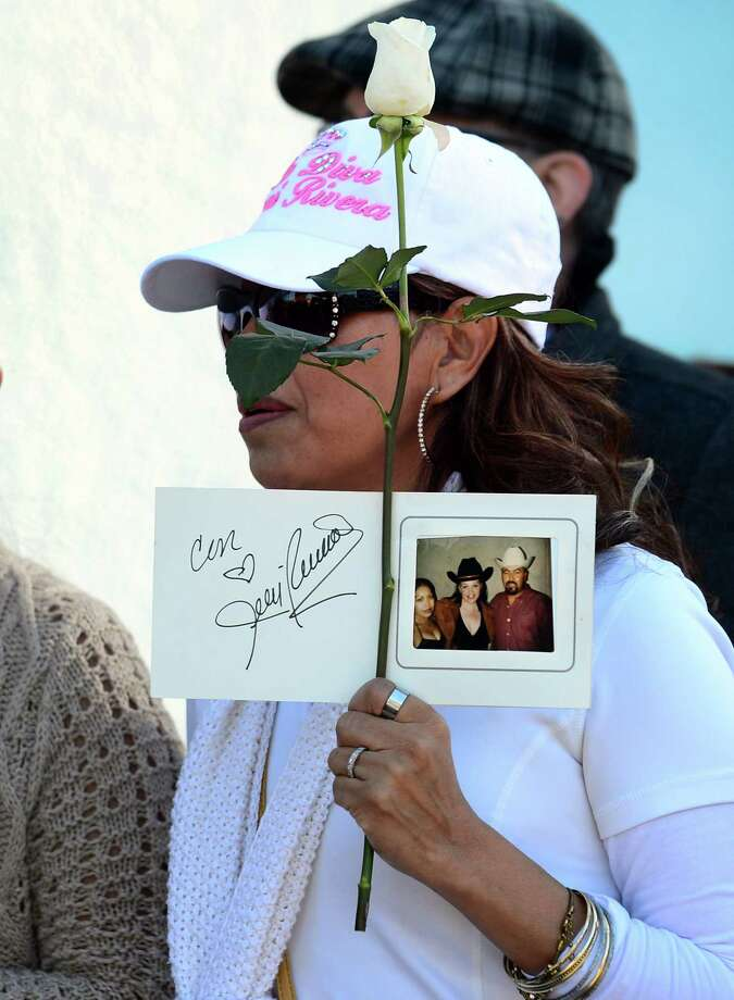 "A woman holds a rose and a photograph in memory of late Mexican-American singer Jenni Rivera as fans wait to attend the memorial service at the Gibson Amphitheater in Universal City on December 19, 2012 in California. The service, billed by the Rivera family as a ""Celestial Graduation,'' was broadcast live and watched by her many fans off a big screen at a Universal CityWalk plaza. Photo: FREDERIC J. BROWN, AFP/Getty Images / AFP"