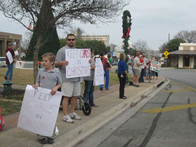Gavin Liss and Ollie Liss (from left) were among those who gathered Wednesday on New Braunfels' Main Plaza in support of the banners put up by the local Knights of Columbus to remind Christians of the holiday's focus. Photo: Courtesy