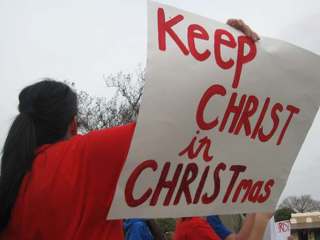 Gypsie Judice holds a sign on New Braunfels' Main Plaza in support of the banners put up by the local Knights of Columbus to remind Christians of the holiday's focus. Photo: Courtesy
