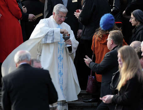 A priest gives communion to mourners standing outside the full St. Mary of the Assumption Roman Catholic Church in Katonah, NY, during the funeral of Sandy Hook Elementary School Special Education teacher Anne Marie Murphy on Thursday, December 20, 2012. Photo: Lindsay Niegelberg, Niegelberg / Stamford Advocate