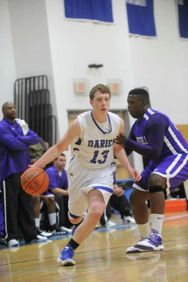 Darien's Liam Naughton moves the ball past Westhill's Aaron Young as Darien High School hosts Westhill in a boys basketball game in Darien, Conn., January 3, 2012. Photo: Keelin Daly / Stamford Advocate