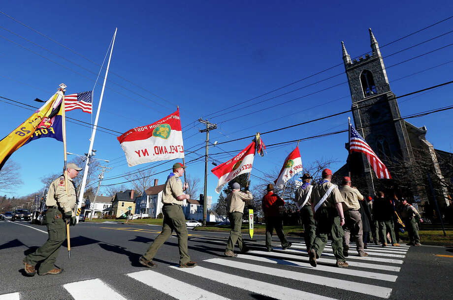 People wearing Boy Scouts of America uniforms carry flags as they walk toward Trinity Episcopal Church before funeral services for Benjamin Andrew Wheeler, Thursday, Dec. 20, 2012, in Newtown, Conn. Wheeler, 6, died when the gunman, Adam Lanza, walked into Sandy Hook Elementary School in Newtown, Dec. 14, and opened fire, killing 26 people, including 20 children, before killing himself. Photo: AP