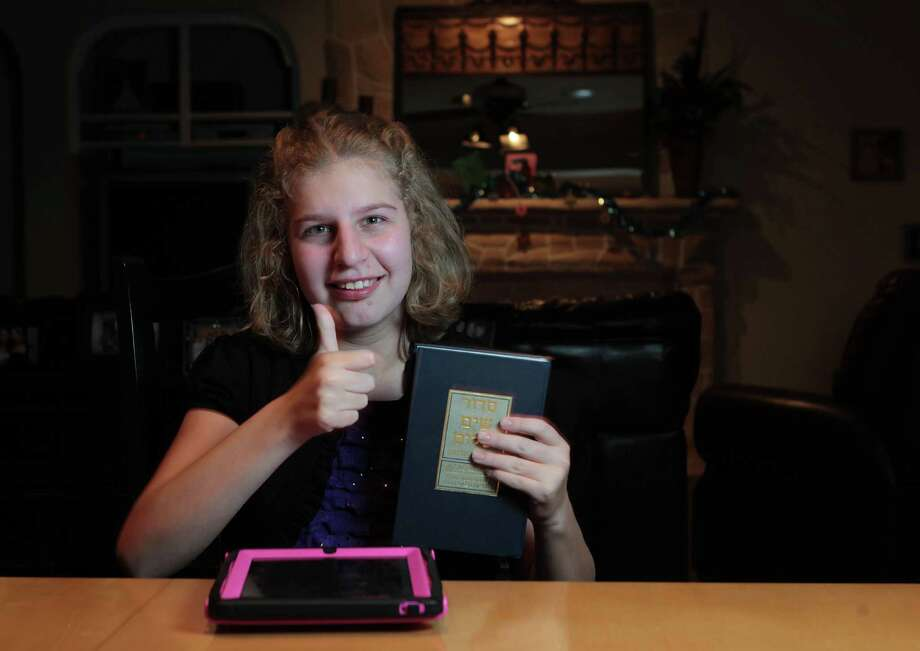 Molly Levinton, who has autism, used an iPad app and a prayer book to help her recite prayers and other required speaking  for her bat mitzvah. Photo: James Nielsen, Staff / © Houston Chronicle 2012