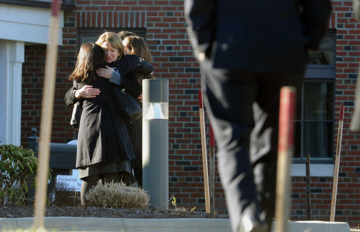 Mourners embrace as they arrive for the funeral for Sandy Hook Elementary School student Allison Wyatt which was held at Sacred Heart Roman Catholic Church in Southbury Conn. on Thursday December 20, 2012.