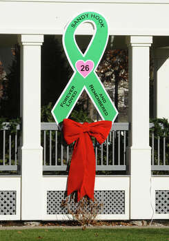 A large green ribbon cutout was placed on the Southbury Green gazebo, placed by workers from Brickman Group, a national landscaping company. They also put up green ribbons on 26 trees on Southbury Green property along Main Street in Southbury Conn. on Thursday December 20, 2012. The ribbons were placed in memory of the victims of the mass shooting at Sandy Hook Elementary School his past Friday. They also placed a tag on each ribbon with a victim's name, including Allison Wyatt, whose funeral was taking place down the street. Photo: Christian Abraham / Connecticut Post