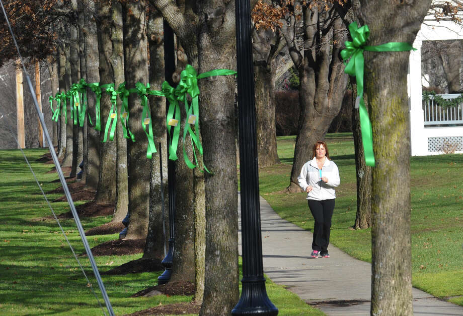 A woman jogs along Main Street after workers from Brickman Group, a national landscaping company, put up green ribbons on 26 trees on Southbury Green property along Main Street in Southbury Conn. on Thursday December 20, 2012. The ribbons were placed in memory of the victims of the mass shooting at Sandy Hook Elementary School his past Friday. They also placed a tag on each ribbon with a victim's name, including Allison Wyatt, whose funeral was taking place down the street. Photo: Christian Abraham / Connecticut Post