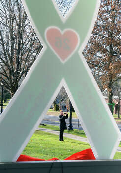 A pedestrian snaps pictures of ribbons placed on the Southbury Green by workers from Brickman Group, a national landscaping company. The green ribbons were placed on 26 trees on Southbury Green property along Main Street in Southbury Conn. on Thursday December 20, 2012. The ribbons were placed in memory of the victims of the mass shooting at Sandy Hook Elementary School his past Friday. They also placed a tag on each ribbon with a victim's name, including Allison Wyatt, whose funeral was taking place down the street. Photo: Christian Abraham / Connecticut Post