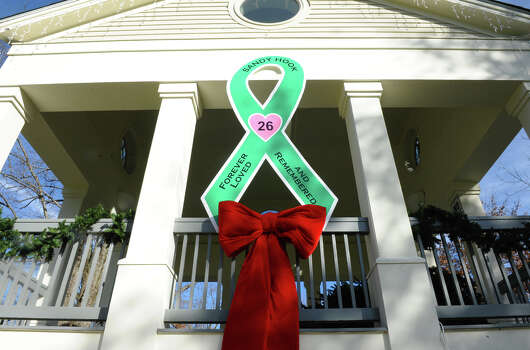 A large green ribbon cutout adorns the Southbury Green gazebo, placed by workers from Brickman Group, a national landscaping company. They also put up green ribbons on 26 trees on Southbury Green property along Main Street in Southbury Conn. on Thursday December 20, 2012. The ribbons were placed in memory of the victims of the mass shooting at Sandy Hook Elementary School his past Friday. They also placed a tag on each ribbon with a victim's name, including Allison Wyatt, whose funeral was taking place down the street. Photo: Christian Abraham / Connecticut Post