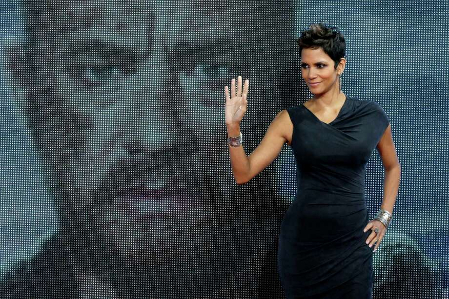 FILE - In this Nov. 5, 2012 file photo, Actress Halle Berry poses for the media in front of a video screen showing the face of actor Tom Hanks during her arrival for the European premiere of the movie 'Cloud Atlas' in Berlin.  Berry and Chaka Khan will be honored at the 2013 BET Honors. The network announced Thursday, Dec. 20, 2012 that basketball star Lisa Leslie, music executive Clarence Avant and religious leader T.D. Jakes will also be celebrated at the Jan. 12 event in Washington, D.C at the Warner Theatre.   (AP Photo/Michael Sohn) Photo: Michael Sohn