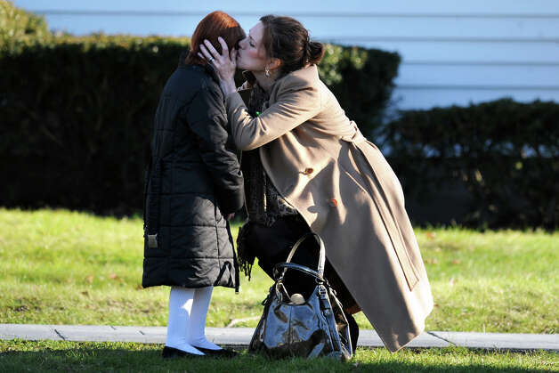 A woman kisses a young girl after leaving the funeral service for Jesse McCord Lewis, at the Honan Funeral Home in Newtown, Conn., Dec. 20th, 2012. Lewis is one of twenty students killed in the mass shooting at Sandy Hook Ele