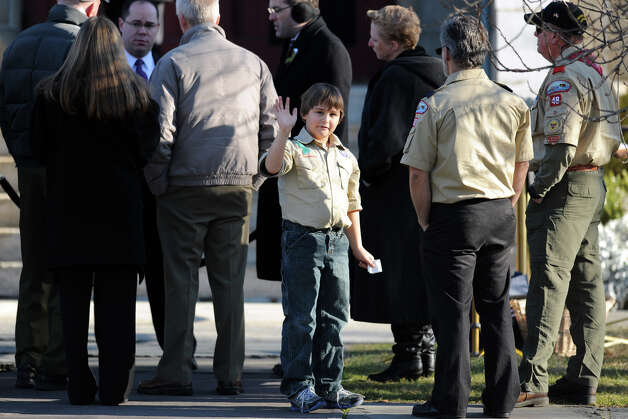 A boy scout waves to the cameras prior to the funeral of Benjamin Wheeler, at Trinity Episcopal Church, in Newtown, Conn., Dec. 20th, 2012. Wheeler is one of twenty students killed in the mass shooting at Sandy Hook Elementary School last Friday. Photo: Ned Gerard / Connecticut Post