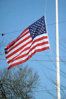 The large flag at the main intersection in Newtown, Conn. remains at half staff Dec. 20th, 2012, in honor of the twenty students killed in the mass shooting at Sandy Hook Elementary School last Friday. Photo: Ned Gerard / Connecticut Post