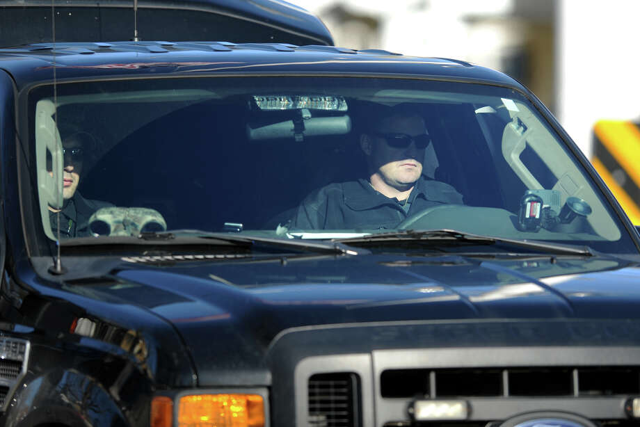Unknown security agents sit watch across the street from the funeral of Benjamin Wheeler, at Trinity Episcopal Church, in Newtown, Conn., Dec. 20th, 2012. Wheeler is one of twenty students killed in the mass shooting at Sandy Hook Elementary School last Friday. Photo: Ned Gerard / Connecticut Post