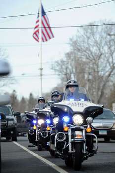 Police motorcycles follwo the hearse carrying the body of Benjamin Wheeler drives down Main Street following his funeral at Trinity Episcopal Church, in Newtown, Conn., Dec. 20th, 2012. Wheeler is one of twenty students killed in the mass shooting at Sandy Hook Elementary School last Friday. Photo: Ned Gerard / Connecticut Post