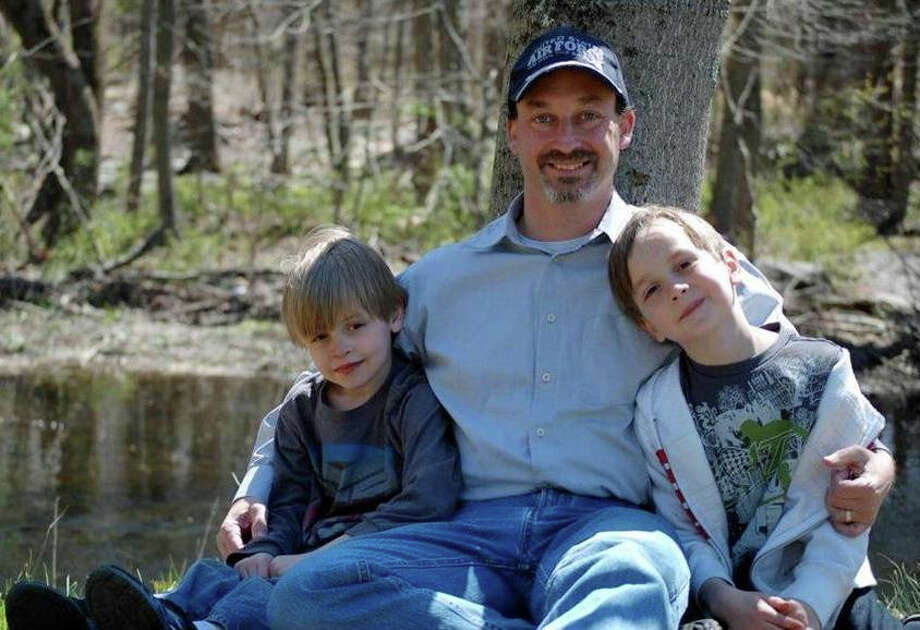 Michael Holms, a Norwalk police officer and now author, with his sons. Photo: Contributed Photo