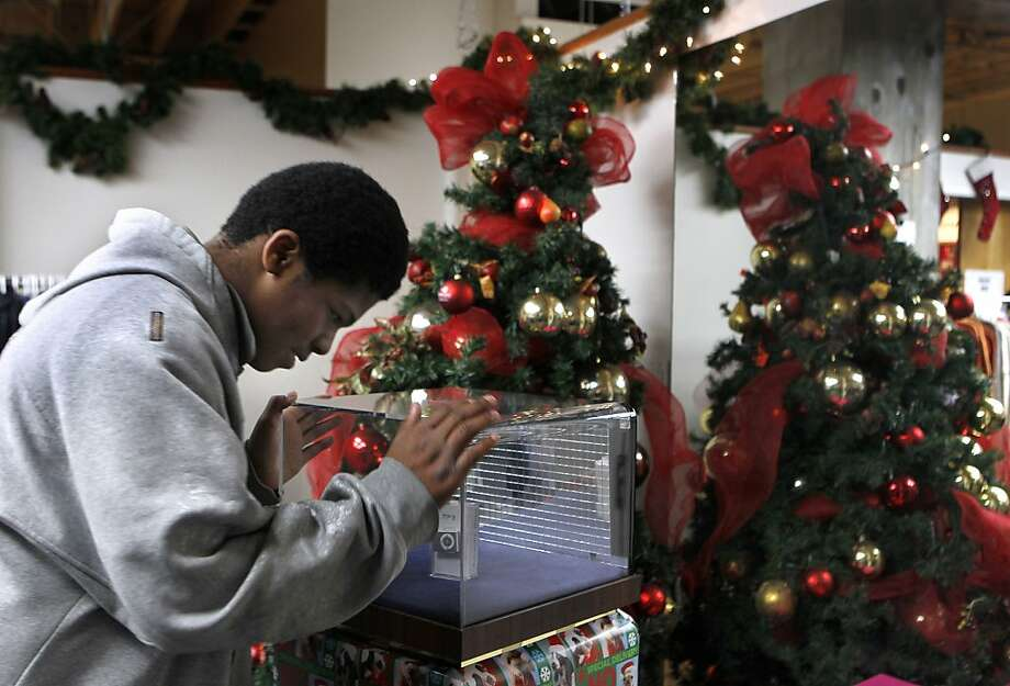 At a Salvation Army holiday toy giveaway in S.F., Renado Tims, 13, settles on an MP3 player (behind glass). Photo: Paul Chinn, The Chronicle