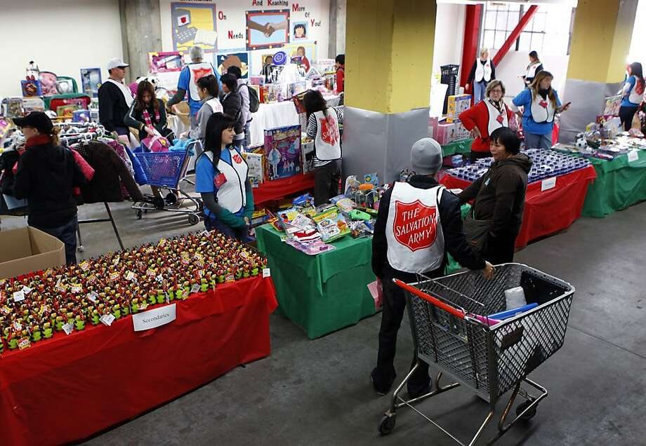 Volunteers help families choose gifts at a Salvation Army holiday toy giveaway in San Francisco, Calif. on Thursday, Dec. 20, 2012. Photo: Paul Chinn, The Chronicle