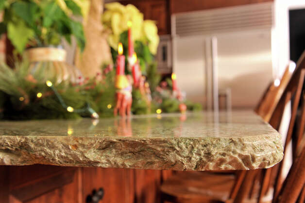The island granite has rough-hewned edges in the Randy Rodgers kitchen. Photo: Robin Jerstad/For The Express-Ne