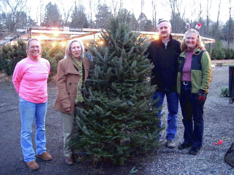 From left, Debbie Gilbertie Gianelli, owner of Weston Gardens; Laura McDonald, of Weston; Paul McDonald; and Lyn Kimberly, market master, stand with a balsam tree, donated by Weston Gardens and won by McDonald during the market's recent Christmas tree raffle. Photo: Contributed Photo