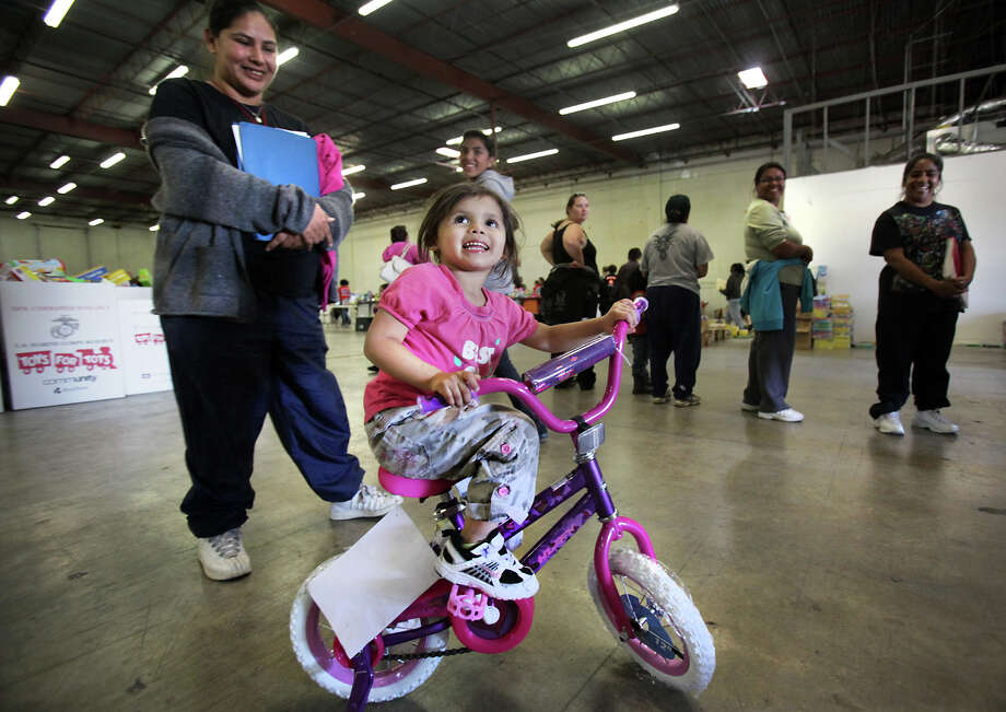 Kadaisy Carreon, 3, smiles as she gets to ride her first bike. She received the gift through the Toys for Tots program. Photo: Bob Owen, San Antonio Express-News / © 2012 San Antonio Express-News