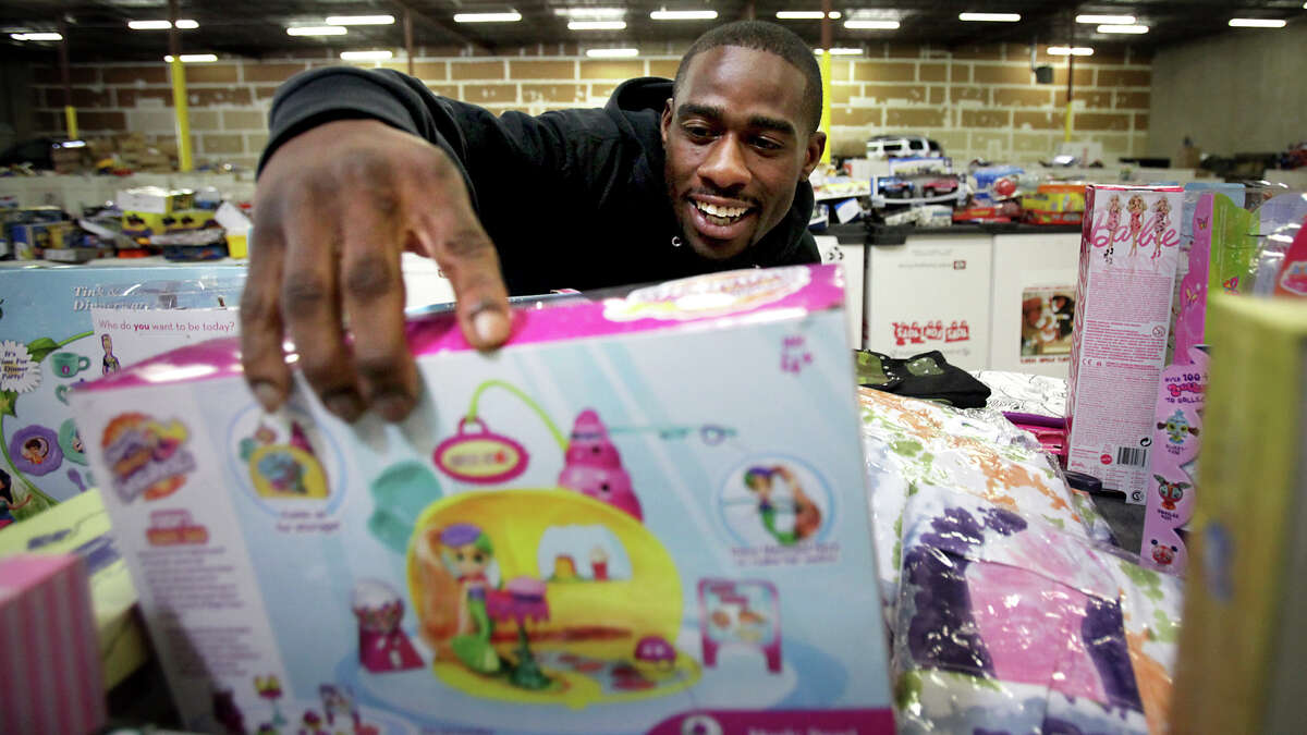 Volunteer Alton Alston picks out a little girl toy for a family at the U.S. Marine Corps Reserve Toys for Tots. More than 5000 families in need of assistance this Christmas requested aid this year. Thursday, Dec. 20, 2012.