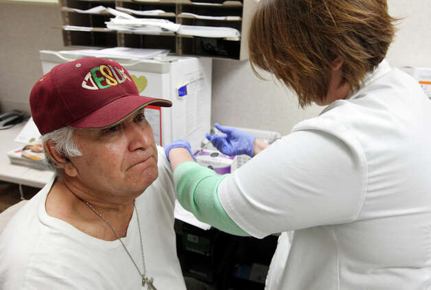Manuel Reyes, 65, gets a flu shot from Walgreens staff pharmacist Amina Mhanna at the drugstore in the 7000 block of South Zarzamora Street. Photo: Edward A. Ornelas, San Antonio Express-News / © 2012 San Antonio Express-News