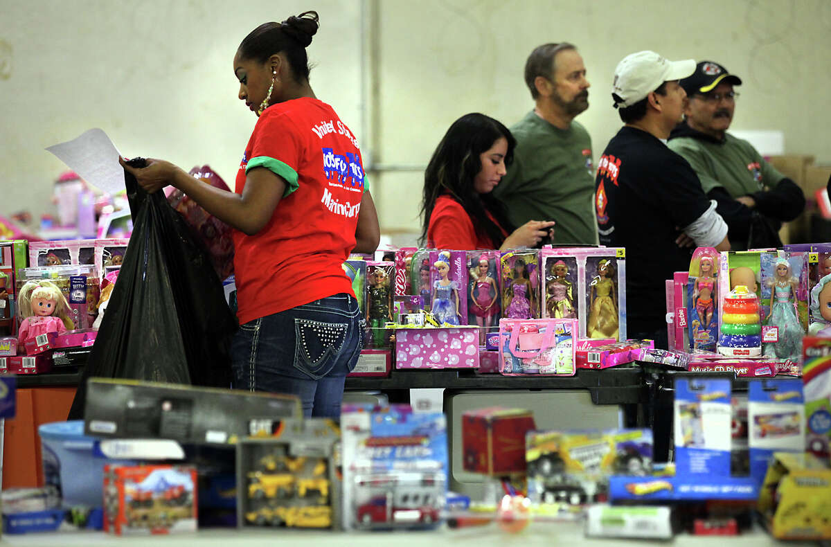 Volunteer Brittany Williams, left, places a toy in a bag for a family at the U.S. Marine Corps Reserve Toys for Tots program. This year the program received more than 5000 requests from families in need of assistance this Christmas to help out with toys. Thursday, Dec. 20, 2012.