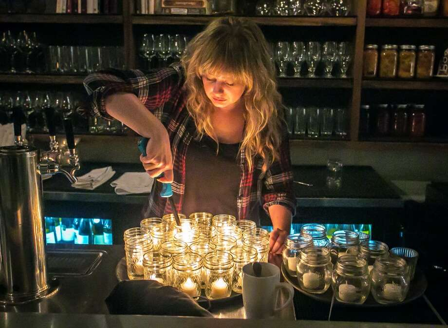 Bartender Sarah Elliott lights candles for the tables (Special to the Chronicle)