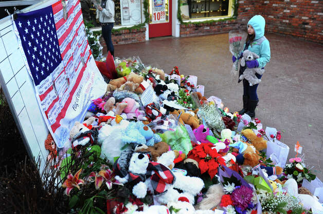 Eight year old Samantha DelGiudice, a third grader at Sandy Hook Elementary School, thinks about where she want to place some flowers and a stuffed animal at a memorial for victims from last Friday's shooting massacre at the school in Newtown, Conn. on Thursday December 20, 2012. Photo: Christian Abraham / Connecticut Post