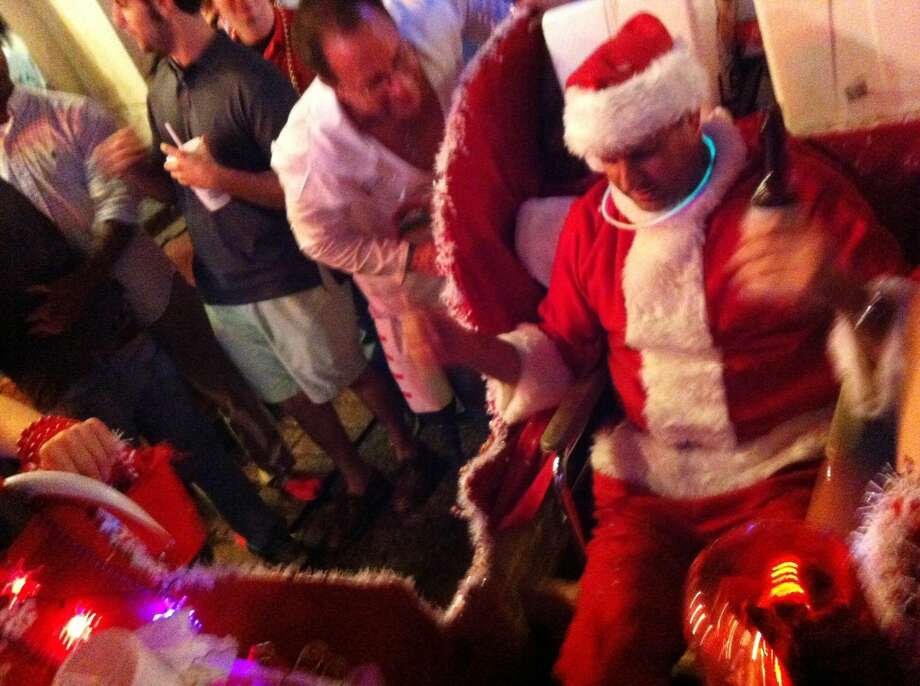 A slightly demented Santa rides down the middle of a packed Bourbon Street on a Saturday night.