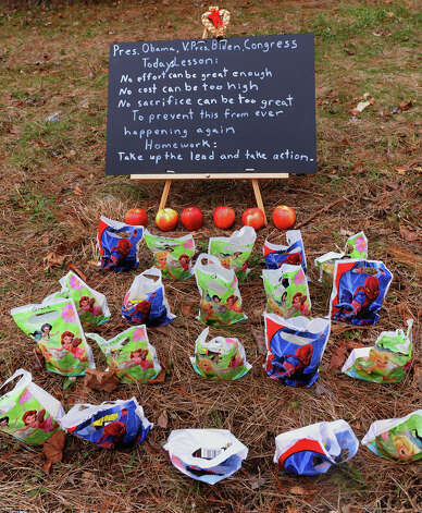 A roadside memorial along Route 34 for victims from last Friday's shooting massacre at Sandy Hook Elementary School in Newtown, Conn. on Thursday December 20, 2012. There are 20 little bags that contained candy to represent the students and 6 apples to represent the teachers who died after a gunman opened fire in the school. Photo: Christian Abraham / Connecticut Post