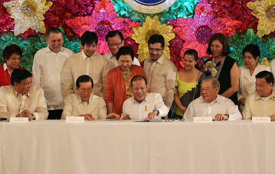 In this photo released by the Malacanang Photo Bureau, Philippine President Benigno S. Aquino III, center, signs into law the Republic Act 10351, Sin Tax Reform Bill 2012, beside, from left, Senate Ways and Means Committee chairman Sen. Franklin Drilon, Senate President Juan Ponce Enrile, House Speaker Feliciano Belmonte, Jr. and House Ways and Means Committee chairman Representative Isidro Ungab at the Malacanang Presidential Palace in Manila, Philippines Thursday, Dec. 20, 2012. Officials hope the bill would raise about 34 billion pesos (about $830 million) annually from higher taxes on tobacco and alcohol to help pay for better public health care. (AP Photo/Malacañang Photo Bureau, Lauro Montellano, Jr.) NO SALES Photo: Lauro Montellano Jr., Associated Press