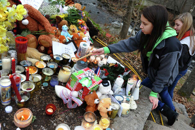 Brookfield student Julianna Sutton re-lights candles blown out at a massive memorial for victims from last Friday's shooting massacre at Sandy Hook Elementary School in Newtown, Conn. on Thursday December 20, 2012. Helping in back is her classmate and friend Moriah Freitag. Photo: Christian Abraham / Connecticut Post