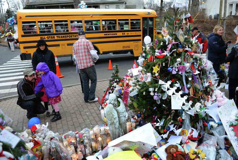 A Newtown schoolbus passes by as people from all over the region gather to view a massive memorial for victims from last Friday's shooting massacre at Sandy Hook Elementary School in Newtown, Conn. on Thursday December 20, 2012. Photo: Christian Abraham / Connecticut Post