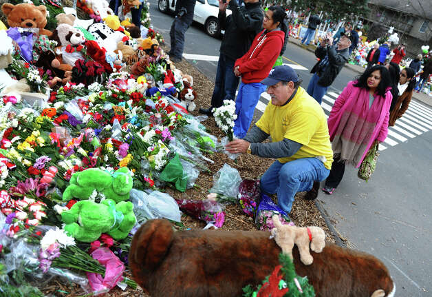 Volunteer Tony Tipton, of Huntingtown, MD, with the organization We Care, helps tidy up flowers set up at a massive memorial for victims from last Friday's shooting massacre at Sandy Hook Elementary School in Newtown, Conn. on Thursday December 20, 2012. Photo: Christian Abraham / Connecticut Post