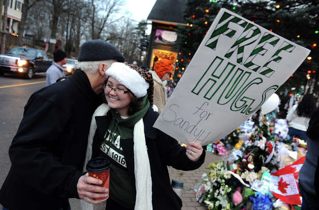 Free hugs were dispensed by a woman from nearby Monroe at a massive memorial for victims from last Friday's shooting massacre at the school in Newtown, Conn. on Thursday December 20, 2012. The women wished to remain anonymous. Photo: Christian Abraham / Connecticut Post