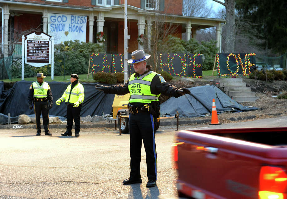 A state trooper directs traffic at the site of a huge memorial set up for victims from last Friday's shooting massacre at Sandy Hook Elementary School in Newtown, Conn. on Thursday December 20, 2012. Photo: Christian Abraham / Connecticut Post