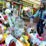 Eight year old Samantha DelGiudice, a third grader at Sandy Hook Elementary School, places some flowers and a stuffed animal at a memorial for victims from last Friday's shooting massacre at the school in Newtown, Conn. on Thursday December 20, 2012.