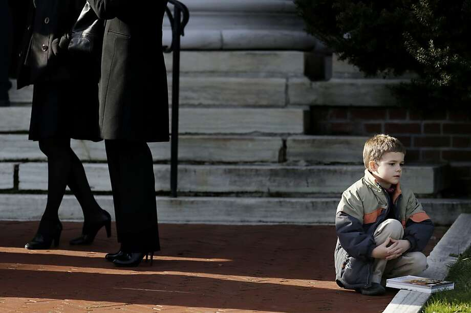 A boy sits near the steps of a church in Danbury, Conn., before the memorial service for Lauren Rousseau, one of the teachers killed in the Sandy Hook Elementary School massacre. Photo: Seth Wenig, Associated Press