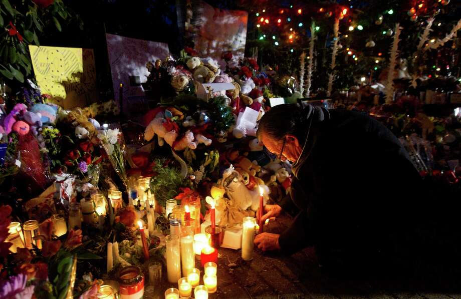 A man lights a candle at a memorial site Thursday, December 20, 2012 in Newtown, Conn., honoring the 26 individuals who were killed during a shooting at Sandy Hook Elementary School last Friday. Photo: Cody Duty, Cody Duty/Hearst Newspapers / The News-Times
